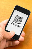 QR code coupon on mobile. By human hand Royalty Free Stock Photo