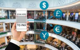 QR code payment concept. Hand wearing business suit holding smartphone display QR code on screen with blurred background of shopping mall. Various currency Royalty Free Stock Photos
