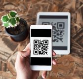 QR code payment transaction using mobile smartphone and tablet devices. Scanning qr code from the tablet using phone. Cashless payment stock photo