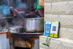 Qr codes for cashless payment stands besides a take-away snack booth. Qr codes for cashless payment with smart phones stands besides a take-away snack booth in royalty free stock photography