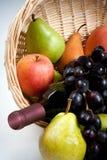 Quälende Frucht im Korb mit Wein-Flasche Lizenzfreie Stockfotos