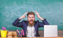 Qué pensamiento estúpido La expresión agresiva del profesor barbudo del hombre sienta el fondo de la pizarra de la sala de clase  fotografía de archivo