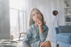 Qué si Niña linda que guarda la mano en la barbilla y que mira awa imagen de archivo libre de regalías