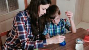 A química experimenta em casa A mamã e o filho fazem uma reação química com a liberação do gás na garrafa filme