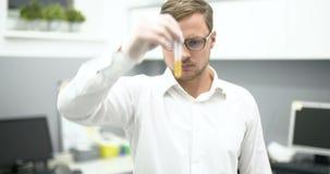 Químico Adding Chemicals en un experimento de mezcla del frasco metrajes