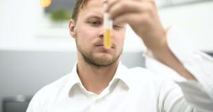 Químico Adding Chemicals en un experimento de mezcla del frasco almacen de video