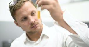 Químico Adding Chemicals en un experimento de mezcla del frasco almacen de metraje de vídeo