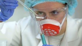 Químico concentrado que mistura reagentes coloridos observando a reação, experiências filme