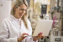 Químico de sexo femenino que trabaja con el ordenador portátil en el laboratorio Fotografía de archivo libre de regalías