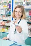 Químico de sexo femenino sonriente que vende las drogas imágenes de archivo libres de regalías