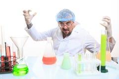 Químico enojado en el laboratorio que hace la reacción Foto de archivo