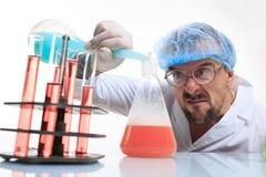 Químico enojado en el laboratorio que hace la reacción Fotos de archivo