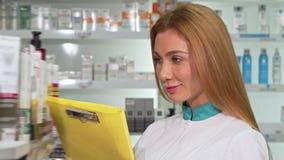 Químico fêmea alegre que sorri à câmera, ao trabalhar na drograria filme