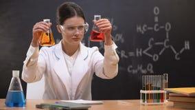 Químico fêmea que mostra líquidos em umas garrafas à câmera, substância nova tornando-se video estoque
