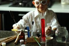 Químico joven del científico que hace muecas mientras que hace sus experimentos científicos imagen de archivo