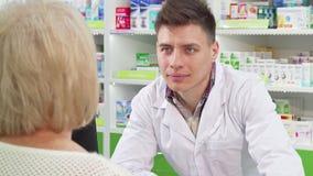 Químico masculino novo atrativo que sorri, falando a seu cliente superior filme
