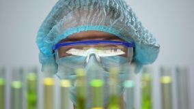 Químico observando la reacción en tubos, producción orgánica de los perfumes, cosmetología metrajes