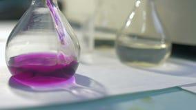 Químico Pouring Liquid To el frasco en el laboratorio almacen de metraje de vídeo