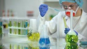 Químico que añade el líquido azul en tubo con la sustancia aceitosa amarilla observando la reacción almacen de video