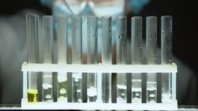 Químico que derrama a substância de borbulhagem líquida no tubo de ensaio, laboratório secreto video estoque