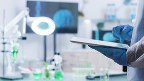 Químico que mecanografía en una tableta digital mientras que lleva guantes metrajes