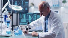 Químico que olha uma amostra vermelha video estoque