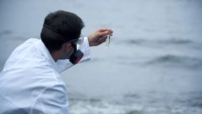 Químico que recoge las muestras de agua, contaminación del océano que lleva a la catástrofe ecológica imagen de archivo