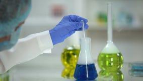 Químico que toma a amostra azul da substância da garrafa, análise do agente de lavagem, teste vídeos de arquivo