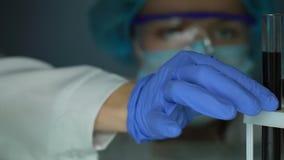 Químico que toma el tubo de ensayo con la sustancia negra del congelador, control de calidad almacen de metraje de vídeo