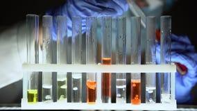 Químico que vierte el líquido rojo en tubos de ensayo y que comprueba la reacción, medicación falsa almacen de metraje de vídeo