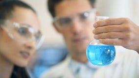 Químicos que trabalham junto e que olham um tubo de ensaio em um laboratório clínico filme