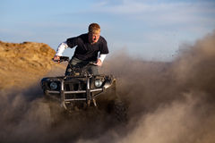 Quad ATV kicking up dust. Teen with funny expression on quad / ATV - four wheeler kicking up dust Royalty Free Stock Images