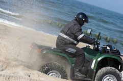 Quad on a beach (ATV). A man riding a quad making twists and turns on the sand. Sea or ocean in the background. Rear wheels deep in the sand, spinning and Stock Photo