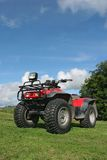 Quad Bike. Four wheel drive quad bike standing idle on the grass with a blue sky and clouds to the rear Royalty Free Stock Photos