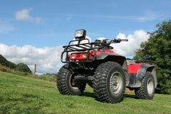 Quad Bike. Four wheel drive red and black quad bike standing idle on the grass, with trees and a blue sky with clouds to the rear Royalty Free Stock Image