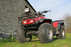 Quad Bike. Four wheel drive red and black quad bike standing idle on the grass Royalty Free Stock Image