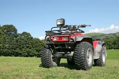Quad Bike. Red and black four wheel drive quad bike standing on the grass in a field in summer with rural countryside and a blue sky to the rear Stock Photography