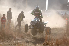 Quad Bike airborne over hump in trail of dust on sand track duri Stock Photo