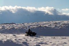 Quad bike ATV. Man riding a quad bike on the snow mountains Royalty Free Stock Photos