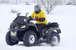 The quad bike driver rides over snow track Royalty Free Stock Photos