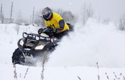 The quad bike driver rides over snow track Royalty Free Stock Images