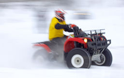 Quad bike driver rides over snow track Royalty Free Stock Photos