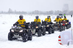 Quad bike drivers rides over snow track Stock Photos