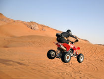 Quad bike jumping in the desert Royalty Free Stock Photo