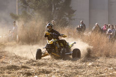 Quad Bike kicking up trail of dust on sand track during rally ra Royalty Free Stock Photos
