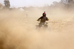 Quad Bike kicking up trail of dust on sand track during rally ra Stock Images