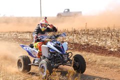 Quad Bike kicking up trail of dust on sand track during rally ra Royalty Free Stock Images