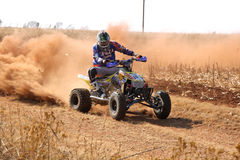 Quad Bike kicking up trail of dust on sand track during rally ra Royalty Free Stock Photography