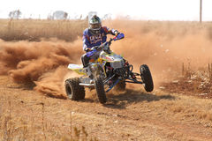 Quad Bike kicking up trail of dust on sand track during rally ra Royalty Free Stock Photo