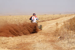 Quad Bike kicking up trail of dust on sand track during rally ra Stock Image
